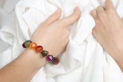 Flickas händer med det flerfärgade armbandet fotografering för bildbyråer