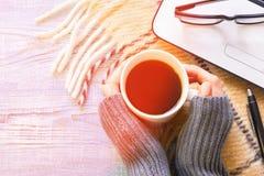 Flickas händer som rymmer en kopp kaffe, när göra bärbar datorarbete med exponeringsglas på en kall solig dag arkivbild