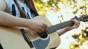Flickas händer som spelar den akustiska gitarren, slut upp stock video