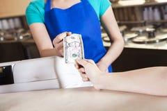 Flickas hand som betalar pengar till arbetaren i glassmottagningsrum Royaltyfri Bild