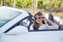 Flickasammanträde bak hjulet av en vitcabriolet Fotografering för Bildbyråer