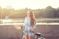 Flickasammanträde bredvid cykeln fotografering för bildbyråer