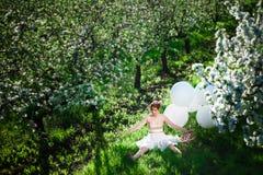Flickasammanträde i äppleträdgården i en dockaställing arkivbilder
