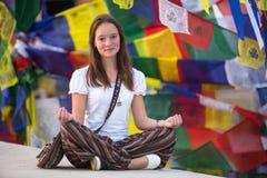 Flickasammanträde i den Lotus positionen på buddistisk stupa Royaltyfria Foton
