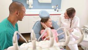 Flickasammanträde i den tand- stolen som ger höjdpunkt fem till tandläkaren och assistenten stock video