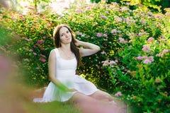 Flickasammanträde i en buske av rosa blommor royaltyfri bild