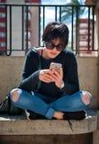 Flickasammanträde i en parkera som kontrollerar hennes mobil Royaltyfri Bild
