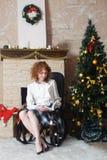 Flickaläsning en boka i inre för nytt år Arkivfoto