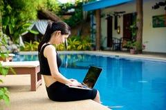 Flickasammanträde med bärbara datorn på pölen Arkivbild