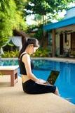 Flickasammanträde med bärbara datorn på pölen Royaltyfria Foton