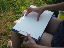 Flickasammanträde med ritbordet, vitt ark av papper Dra på brädet Arkivfoton