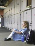 Flickasammanträde mot skolaskåp fotografering för bildbyråer