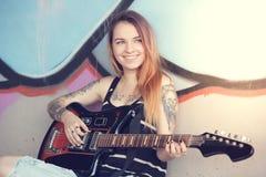 Flickasammanträde nära en grafittivägg och en elektrisk gitarr för lekar Royaltyfri Bild