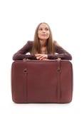 Flickasammanträde nära en resväska som isoleras på vit Arkivfoton