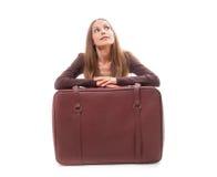 Flickasammanträde nära en resväska som isoleras på vit Royaltyfria Bilder