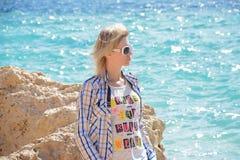 Flickasammanträde nära stenen på stranden Arkivfoton