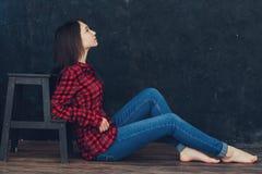 Flickasammanträde nära stolen i studion Royaltyfri Bild