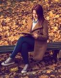 Flickasammanträde på bänk i tillflykt och läsning en bok Fotografering för Bildbyråer