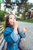 Flickasammanträde på bänk med godisar Arkivbild