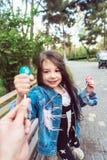 Flickasammanträde på bänk med godisar Arkivfoto