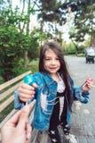 Flickasammanträde på bänk med godisar Fotografering för Bildbyråer