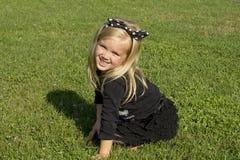 Flickasammanträde på den gröna gräsmattan Royaltyfri Fotografi
