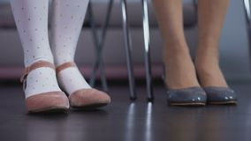 Flickasammanträde på den near modern för stol, rosa skor för stampa playfully och att vänta köen lager videofilmer