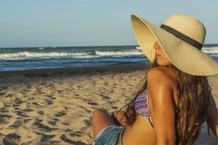 Flickasammanträde på den vända för strandsommar för strand bärande hatten Arkivfoton
