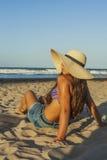 Flickasammanträde på den vända för strandsommar för strand bärande hatten Royaltyfri Fotografi