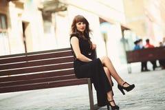 Flickasammanträde på en bänk i staden Royaltyfri Bild