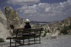 Flickasammanträde på en bank som tycker om majestuosityen av det Capadocia landskapet i Turkiet Fotografering för Bildbyråer