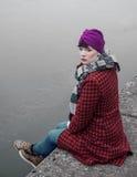 Flickasammanträde på en pir och tänka royaltyfria foton