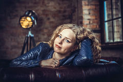 Flickasammanträde på en soffa Arkivfoto