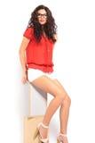 Flickasammanträde på en stol och en fixande hennes hår, medan posera och loo Royaltyfri Foto