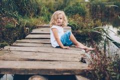 Flickasammanträde på en träpir Royaltyfri Foto