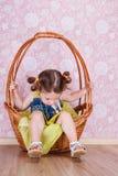 Flickasammanträde på en vide- korg royaltyfria bilder