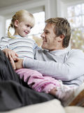 Flickasammanträde på faders Lap In House royaltyfri fotografi