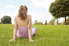 Flickasammanträde på gräs parkerar in. Royaltyfri Bild