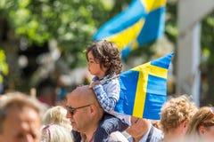 Flickasammanträde på a mans skuldran som rymmer en svensk flagga Royaltyfria Bilder