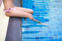 Flickasammanträde på poolsiden med ölexponeringsglas Arkivbild