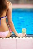 Flickasammanträde på poolsiden med ölexponeringsglas Royaltyfri Fotografi