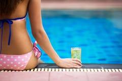 Flickasammanträde på poolsiden med ölexponeringsglas Royaltyfri Bild