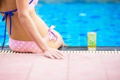 Flickasammanträde på poolsiden med ölexponeringsglas Royaltyfri Foto