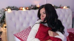 Flickasammanträde på sängen i en omfamning med kudden stock video