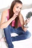 Flickasammanträde på sängen och innehav en avspegla Royaltyfri Foto