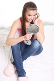 Flickasammanträde på sängen och innehav en avspegla Royaltyfri Fotografi