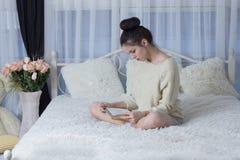 Flickasammanträde på sängen och läsningen en bok Arkivbilder