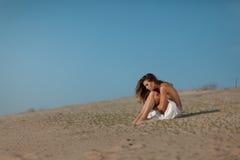 Flickasammanträde på sanden arkivbilder