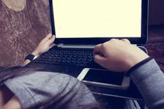 Flickasammanträde på soffan och arbete med bärbara datorn Royaltyfri Bild