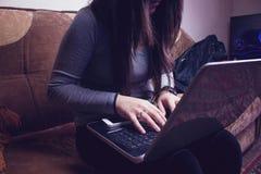 Flickasammanträde på soffan och arbetet Fotografering för Bildbyråer